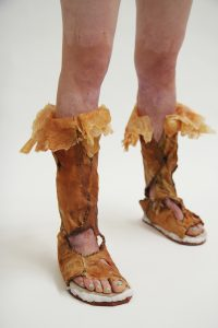 A caucasian model wearing a pair of open-toe, calf-height boots, which are mostly made with latex and plastic. This pair of boots has an uneven skin-like surface, where thick scars form creases and bumps in brownish, orange and beige colors. Skin-like latex pieces lightly drape themselves like flower petals blooming on top of the boots. Large openings on the front and side of the boots reveal the model's burn scars. The model's scars from skin graft surgeries are also revealed on her knees and lower thighs. Black stitches are used to hold the wall of the boots together. The model's toes have turquoise nail polish. Parts of the soles were made with a layer of white plastic, which has an organic, fluid quality.