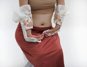 A Caucasian model rests both of her hands on her hips. She wears a coral colored skirt and a beige bandeau, which is a strip of garment covering her breasts. A pair of white, L-shaped wrist braces cradle her wrists, which naturally curve inwards. Her fingers curve and rest gently next to each other. The L-shaped braces have a hard surface, but with organic, wavy edges close to the model's hands. The model's forearms are cuffed with soft and creamy fabric embroidered with clusters of white and pinkish French knots (tiny ball shaped stitches). A thin mesh fabric forms ruffles on the top of the braces. The model sits on a chair wrapped in white fabric.