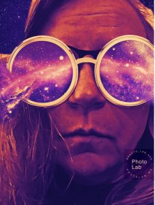 Stylized selfie of the author in a violet purple hue, unsmiling, wearing artistically rendered glasses that have circular lenses with an outer space background. Starry, purple nebulae are exploding out of each lens to the left and right. In the lower right-hand side is a semi-transparent watermark with #PHOTOLAB and photolab.me.